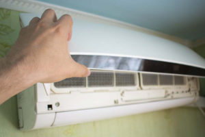 A hand adjusting the settings on an air conditioner | Air Conditioner Short Cycling | Is It Normal for My AC to Turn On and Off? | Aberdeen, NC