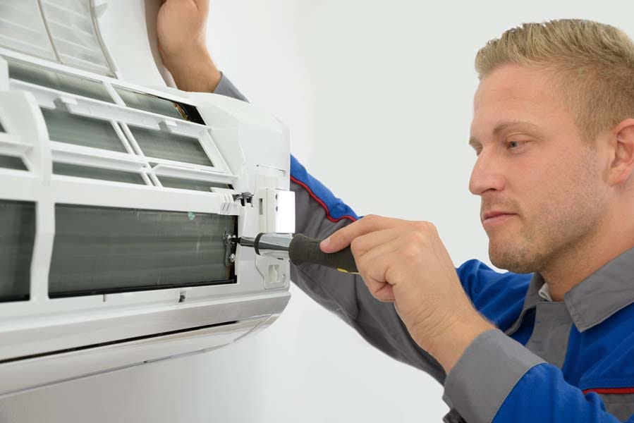 Portrait Of Young Male Technician Repairing Air Conditioner in Aberdeen, NC