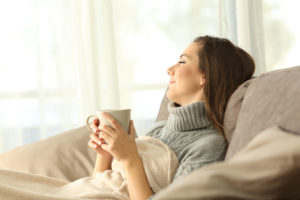 Portrait of a pensive woman relaxing sitting on a sofa in the living room in a house interior in winter enjoying her zone control system